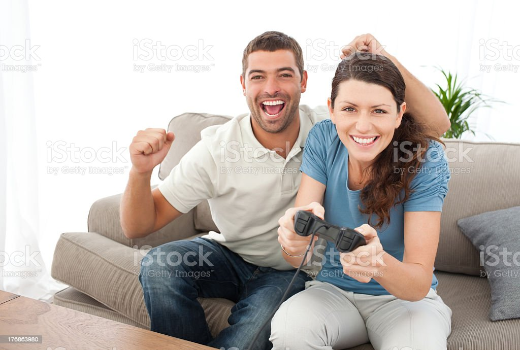 Cheerful man encouraging his girlfriend playing video game royalty-free stock photo