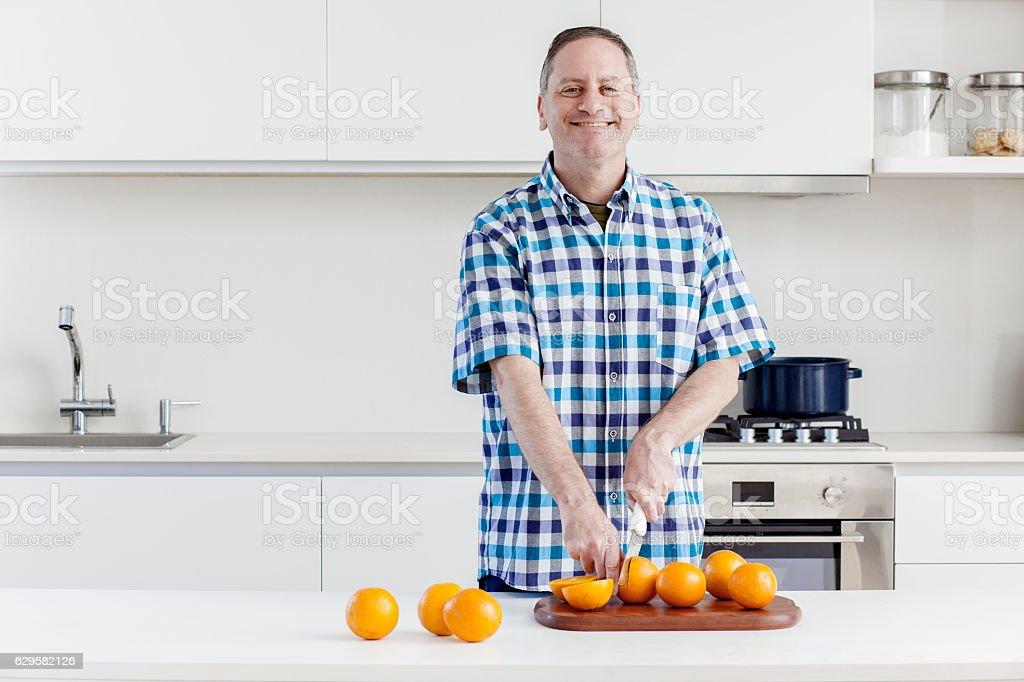 Cheerful man halving oranges stock photo