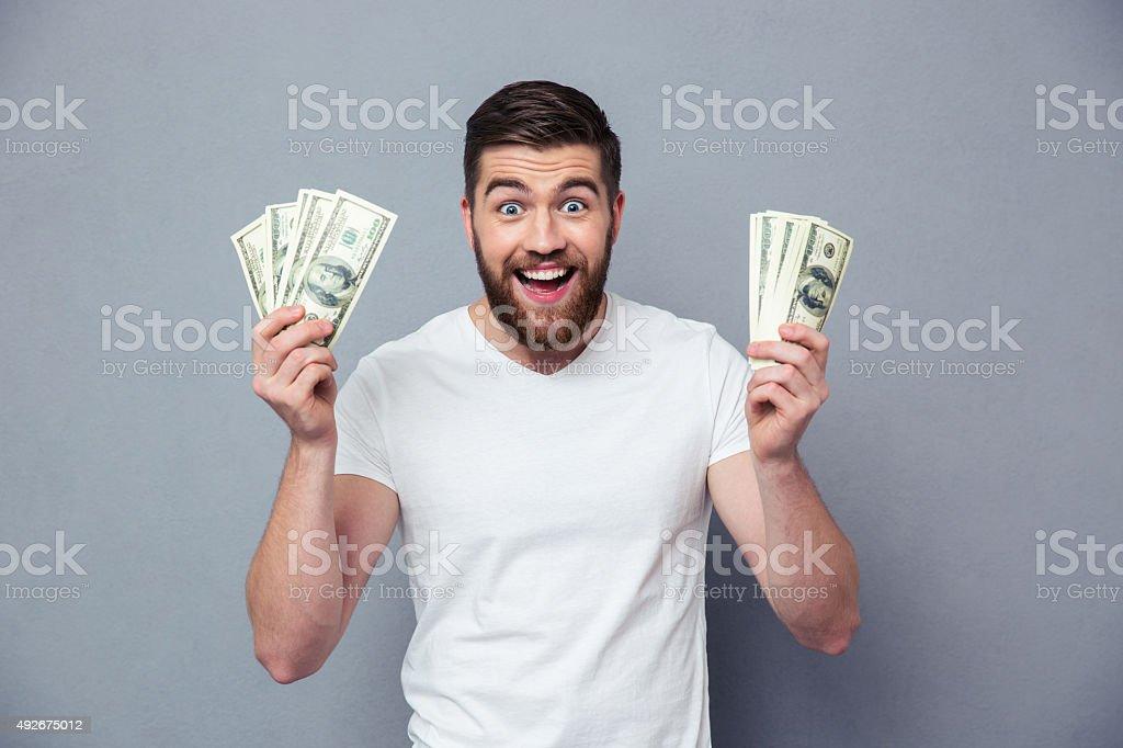 Cheerful man holding dollar bills stock photo