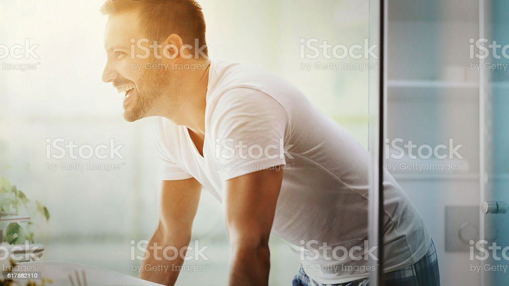 Cheerful man in bathroom. stock photo