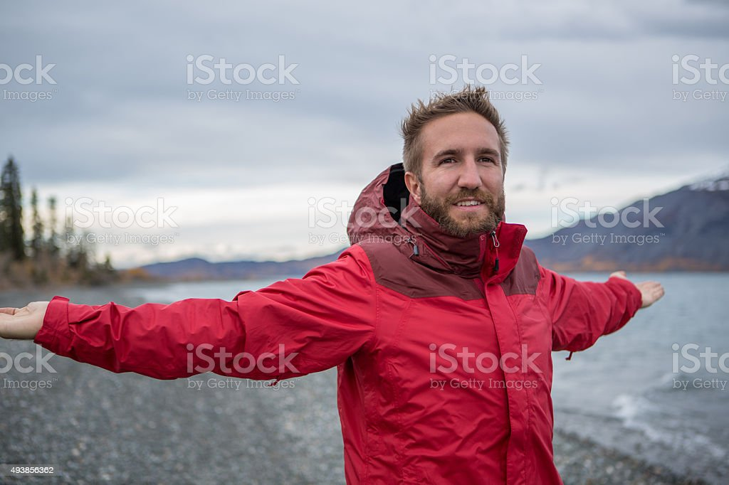Cheerful man in nature arms outstretched for positive emotion stock photo