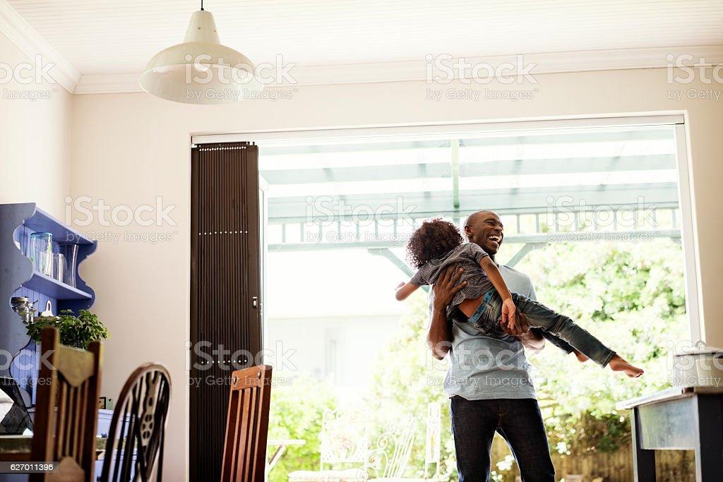 Cheerful man lifting boy at home stock photo