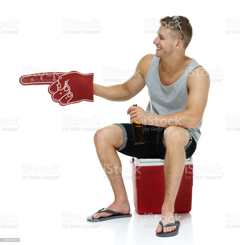 Cheerful man on cooler and pointing away stock photo
