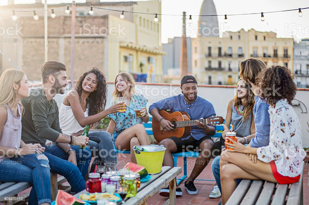 Cheerful man playing guitar for friends on terrace stock photo
