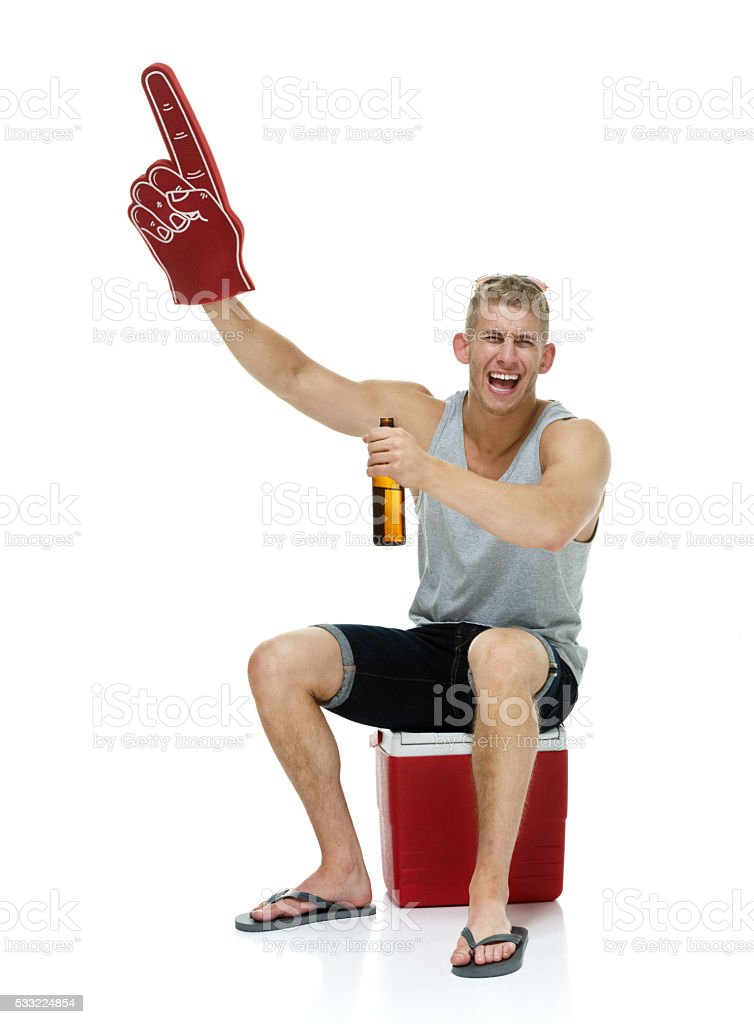 Cheerful man pointing while holding beer bottle stock photo