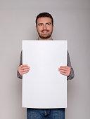 cheerful man presenting a white cardboard