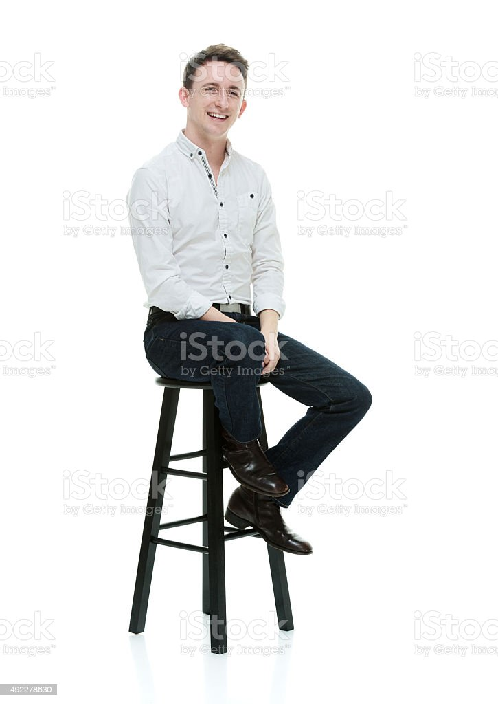 Cheerful man sitting on stool and looking at camera stock photo