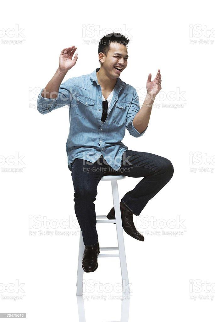 Cheerful man sitting on stool stock photo