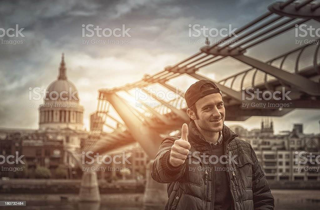 Cheerful man standing in front of the Millenium bridge royalty-free stock photo