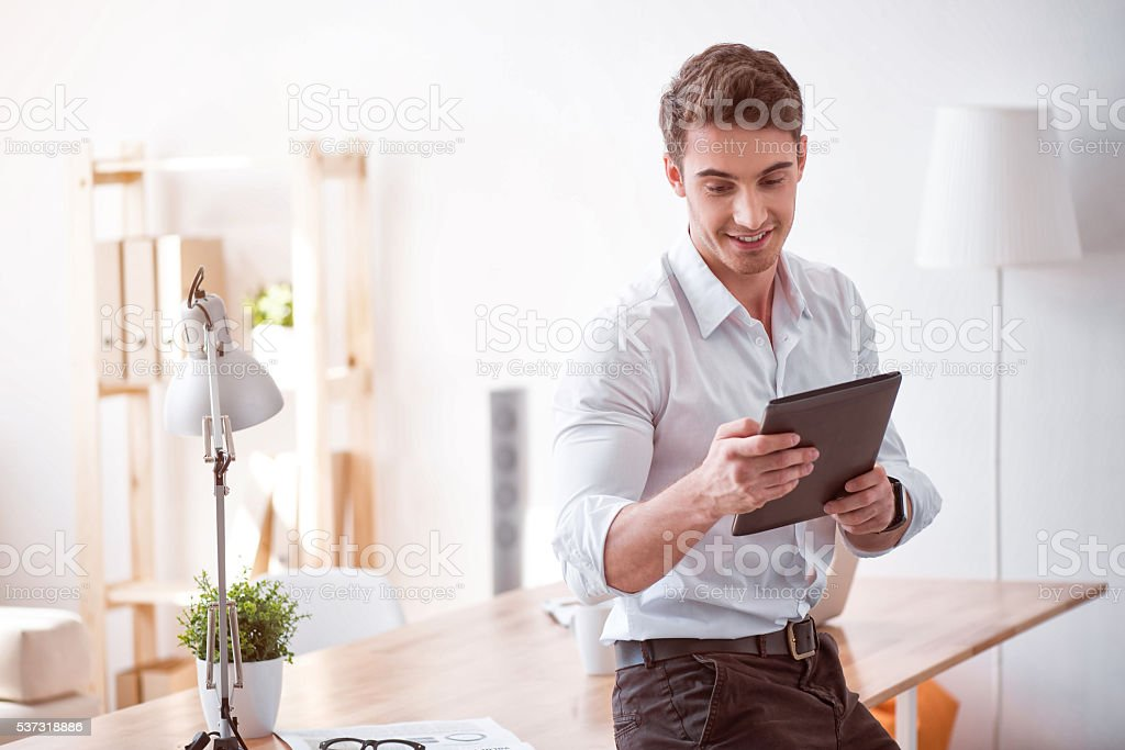 Cheerful man using tablet stock photo