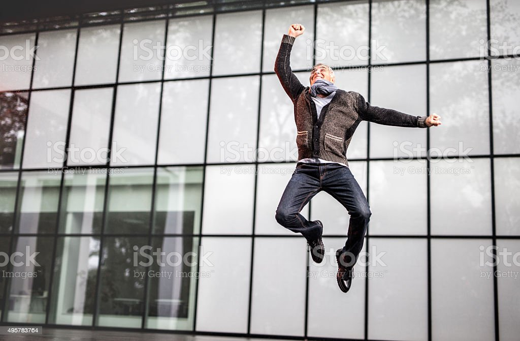 Cheerful mature businessman jumping in front of an office building. stock photo