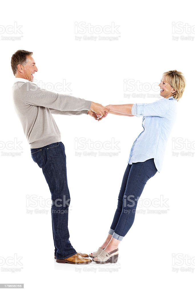 Cheerful mature couple holding hands standing on white royalty-free stock photo
