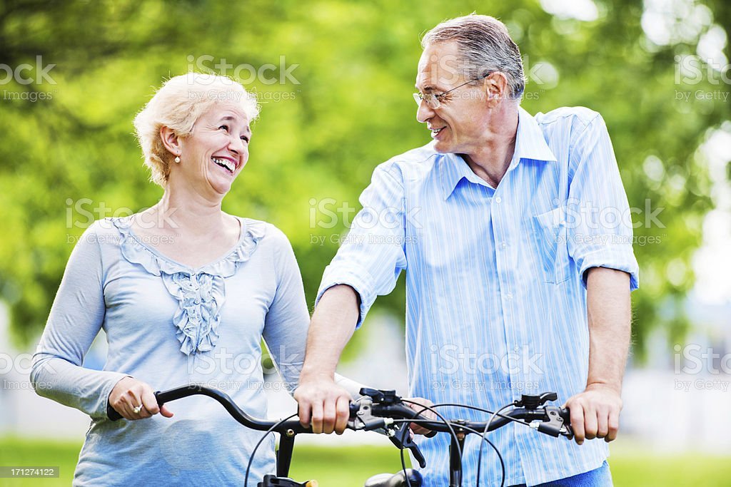 Cheerful mature couple riding bicycles in park. royalty-free stock photo