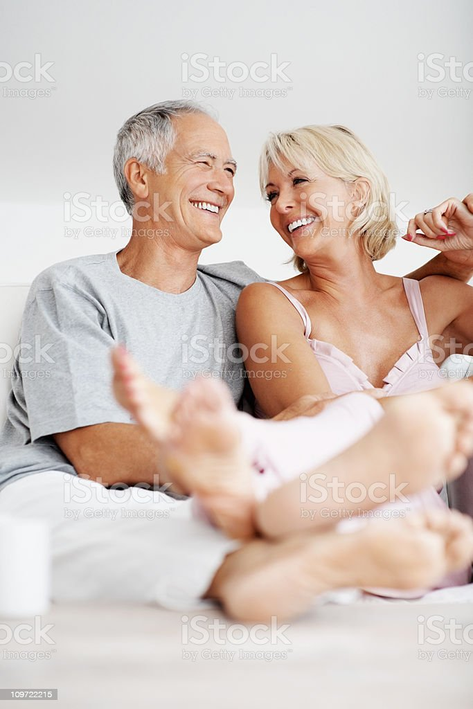 Cheerful mature couple sitting together in sofa royalty-free stock photo
