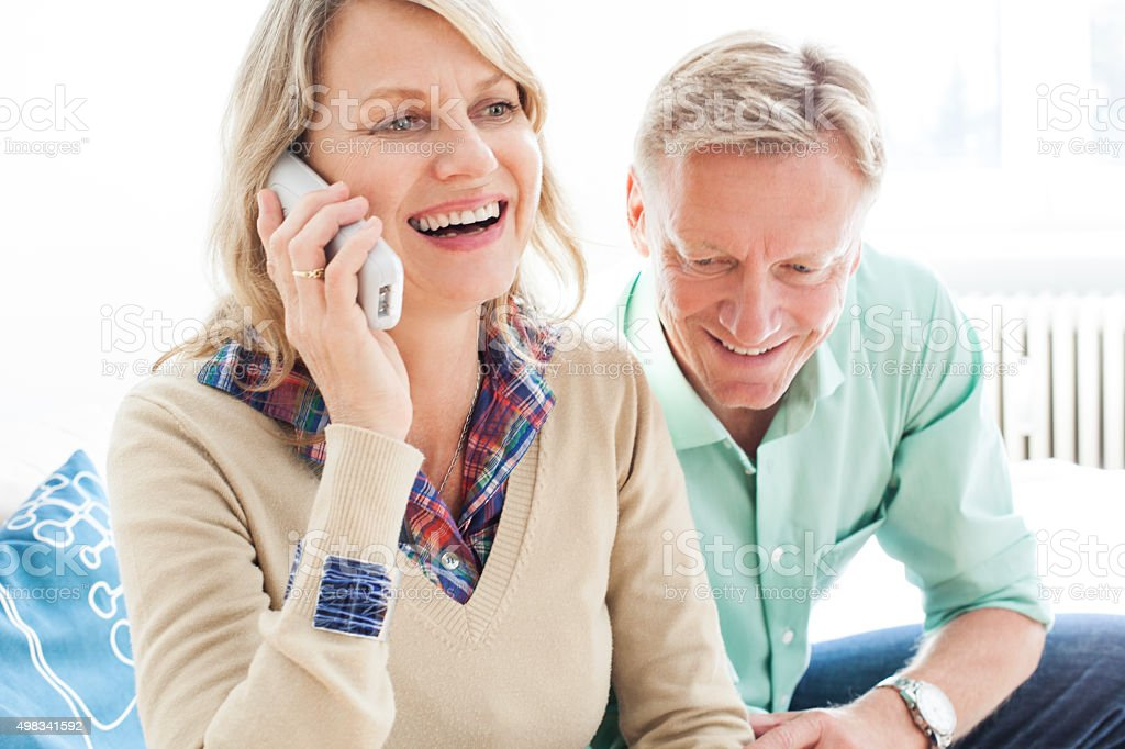 Cheerful mature couple speaking on a phone stock photo