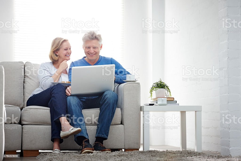 Cheerful mature couple using laptop computer at home stock photo