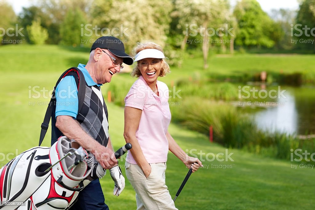 Cheerful mature couple walking on a golf course stock photo