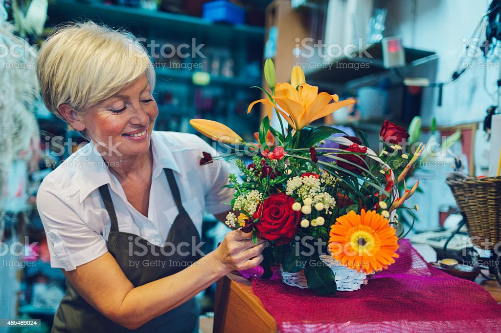 Cheerful mature florist making bouquet in her shop. stock photo