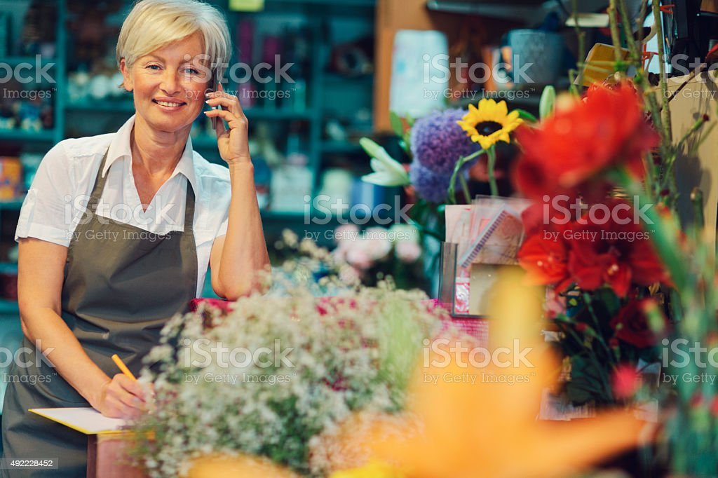 Cheerful mature florist talking on the phone in her shop. stock photo