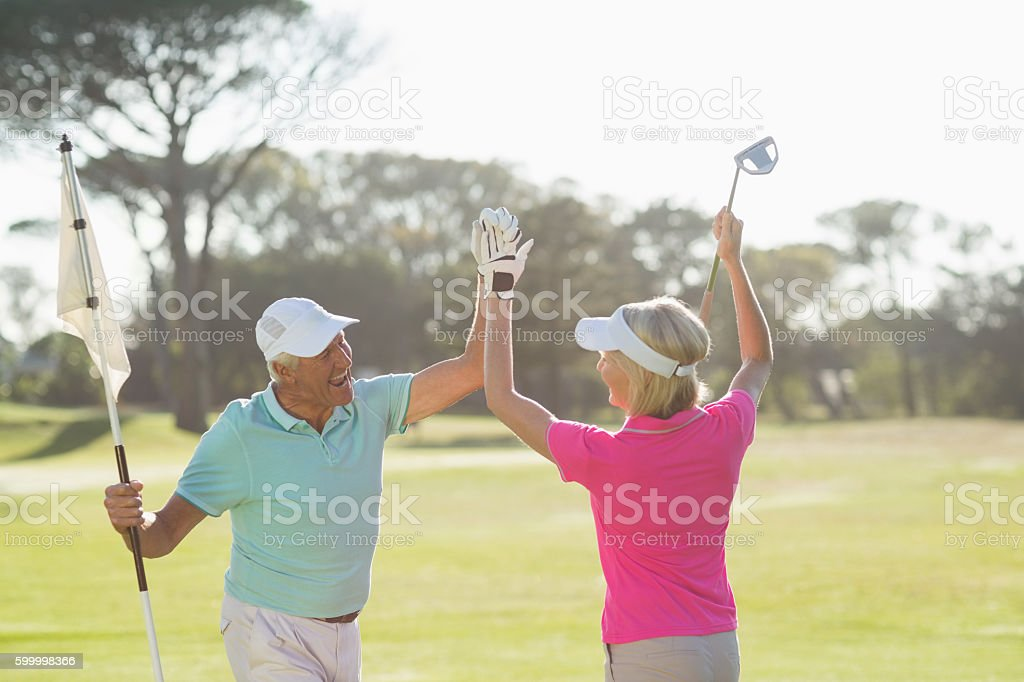 Cheerful mature golfer couple giving high five stock photo