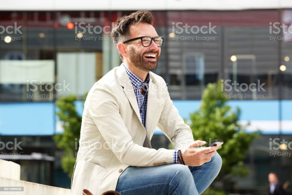 Cheerful mature guy sitting outdoors with cellphone stock photo