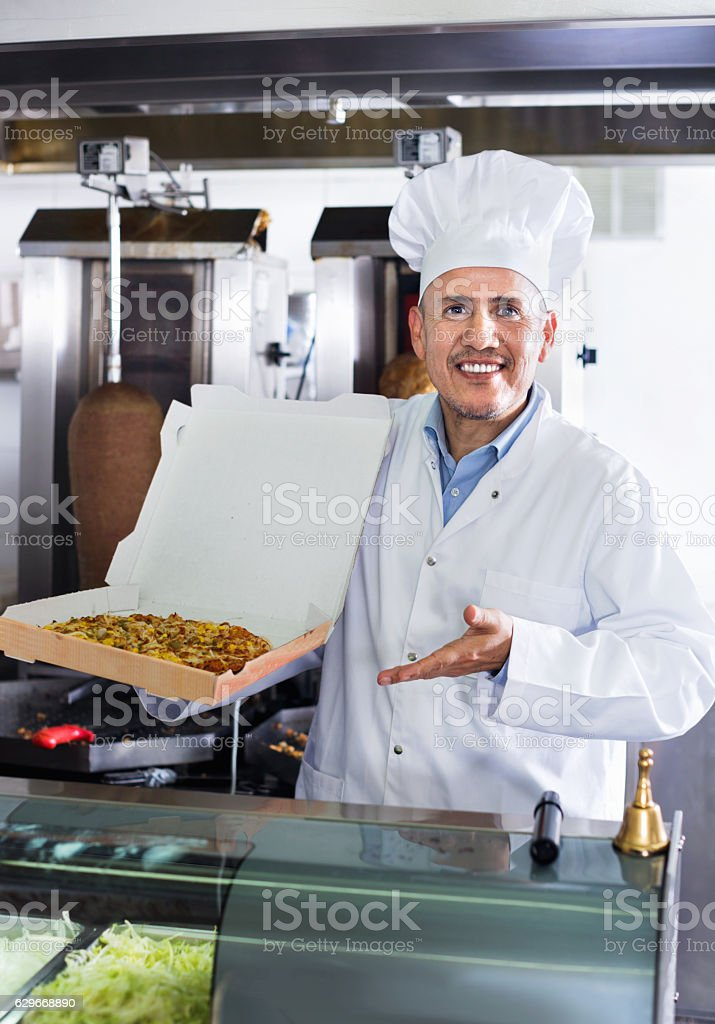 Cheerful mature man cook giving freshly made pizza stock photo