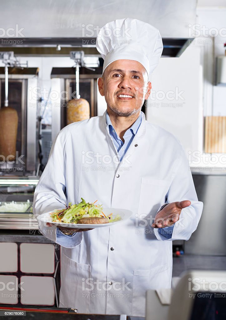 Cheerful mature man cook serving fresh kebab dish on plate stock photo