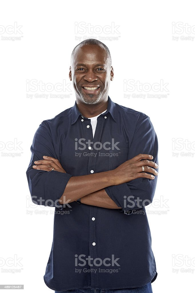 Cheerful mature man standing with his arms crossed against white stock photo