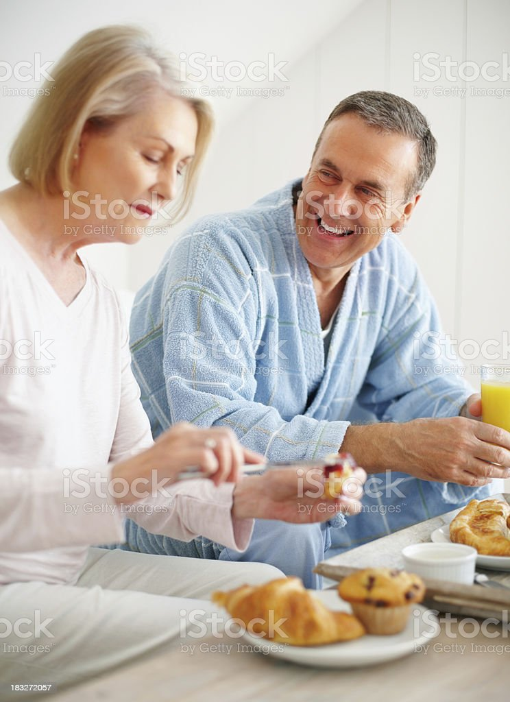 Cheerful mature man with wife having breakfast at home royalty-free stock photo