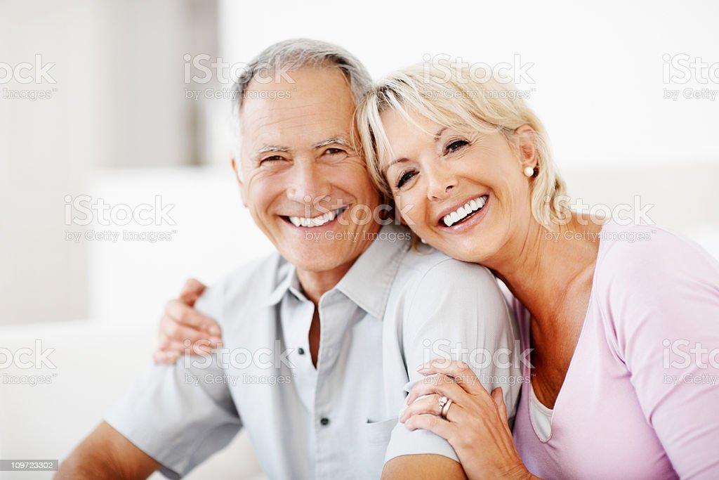 Cheerful mature woman embracing senior man against white stock photo