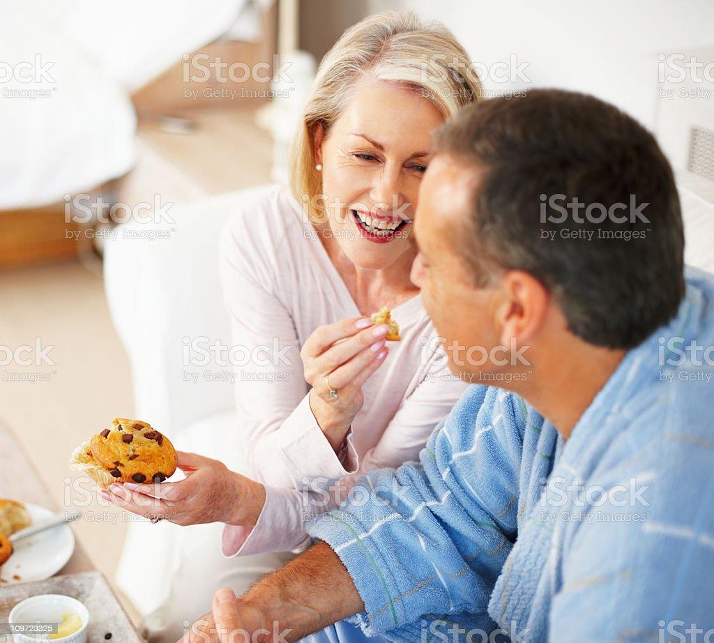 Cheerful mature woman feeding Muffin to husband royalty-free stock photo