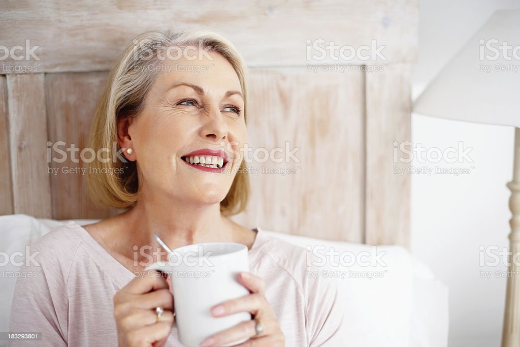 Cheerful mature woman holding coffee mug royalty-free stock photo