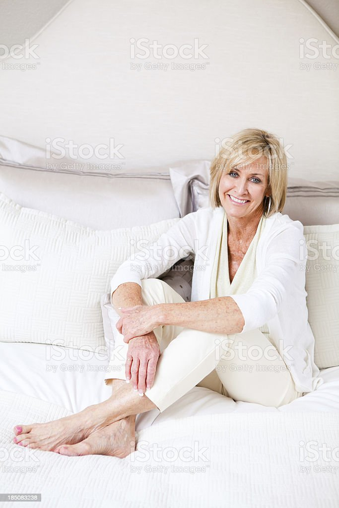 Cheerful mature woman relaxing on a bed royalty-free stock photo