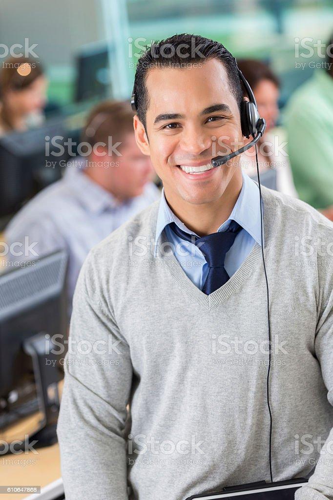 Cheerful mid adult Hispanic call center operator stock photo