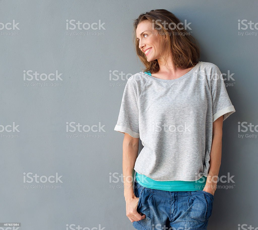 Cheerful mid adult woman smiling and looking to the side stock photo