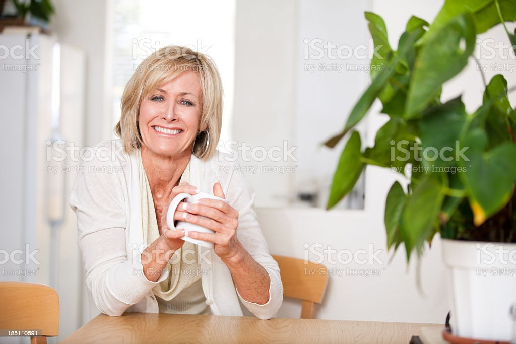 Cheerful middle aged woman enjoying hot tea stock photo