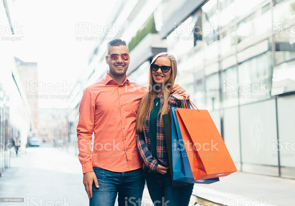 Cheerful modern couple in weekend shopping stock photo