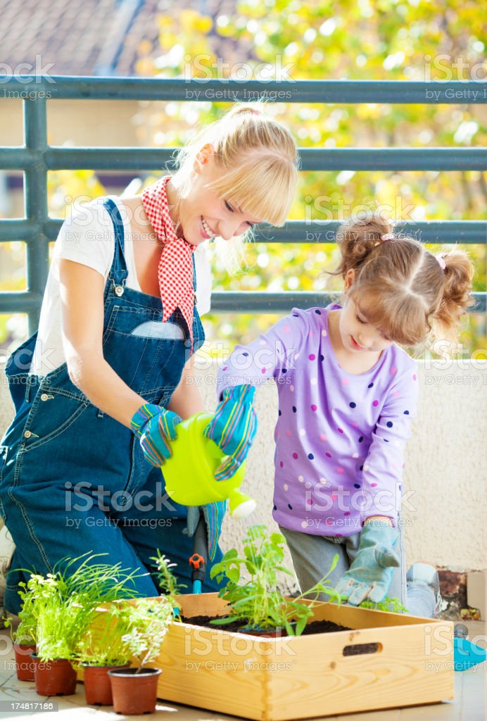 Cheerful Mother and Child Gardening at home balcony. royalty-free stock photo