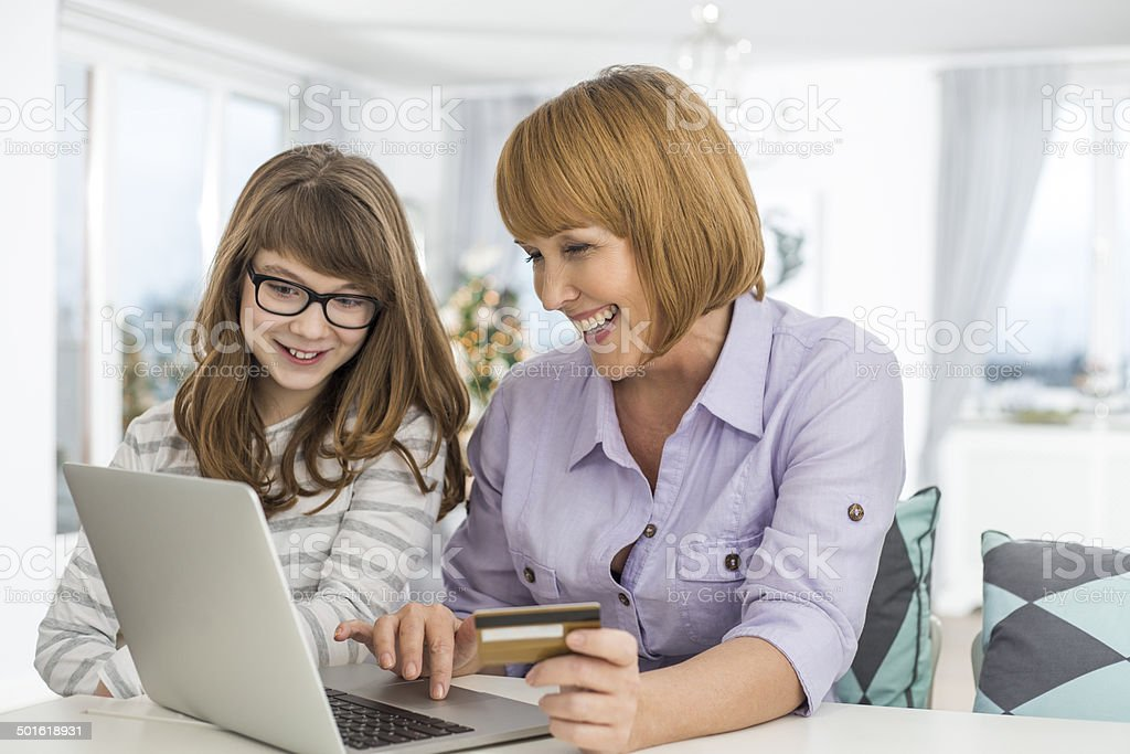 Cheerful mother and daughter shopping online at home during Christmas stock photo