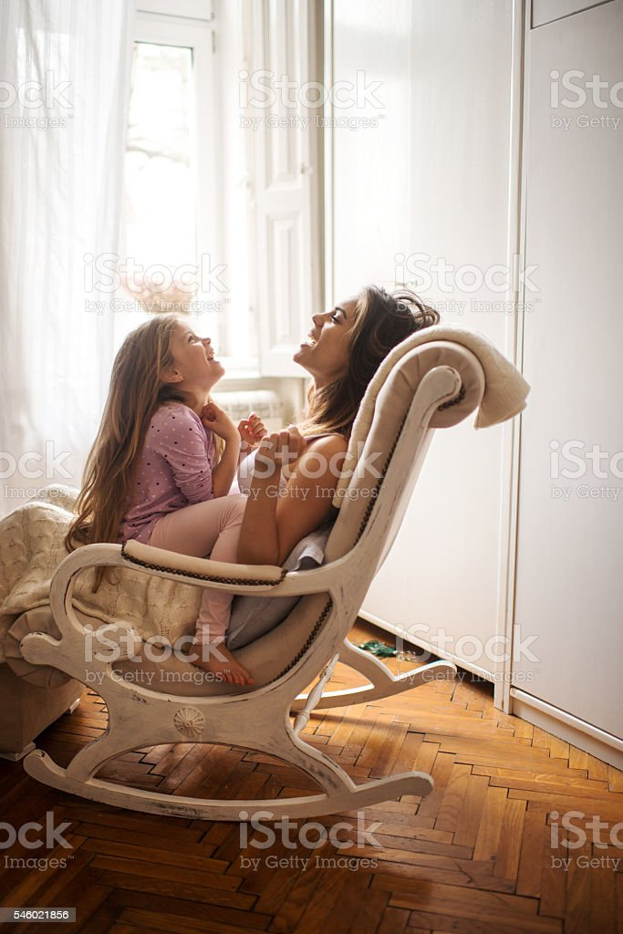 Cheerful mother and daughter sitting in rocking chair and laughing. stock photo