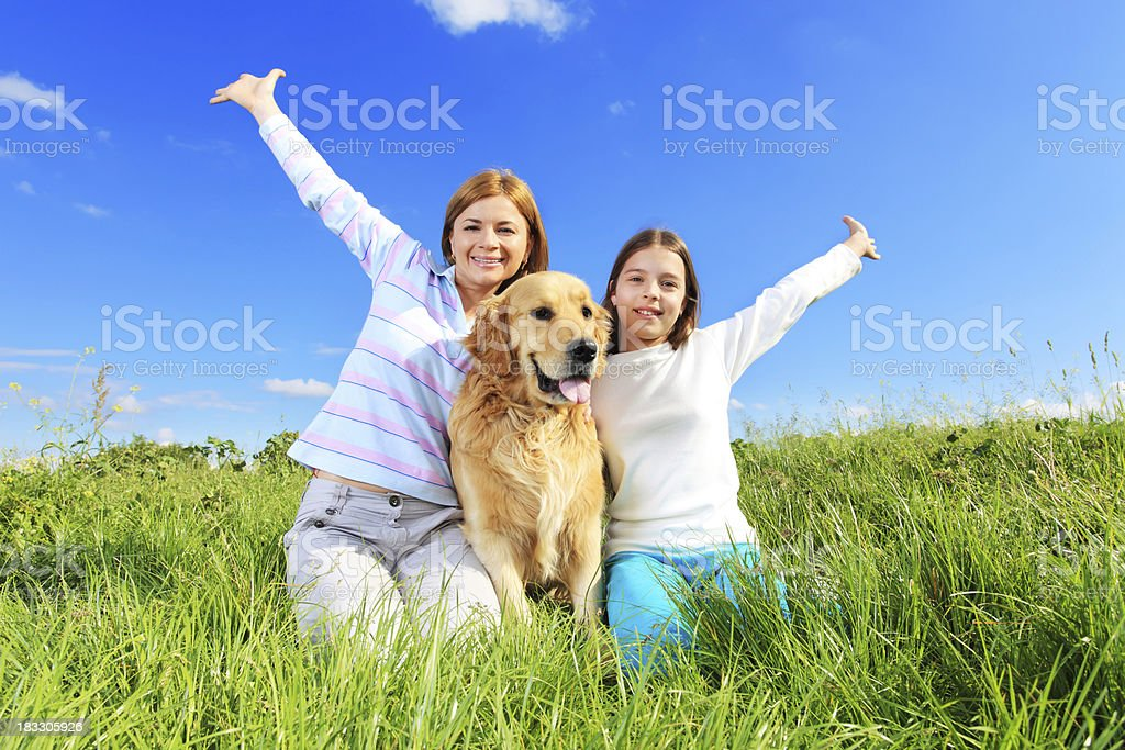 Cheerful mother, daughter and dog spends day outside. royalty-free stock photo