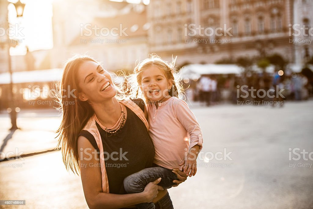 Cheerful mother enjoying with her daughter in the city. stock photo