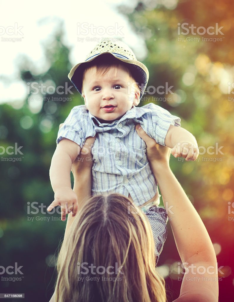 Cheerful mother holding aloft her son outdoors stock photo