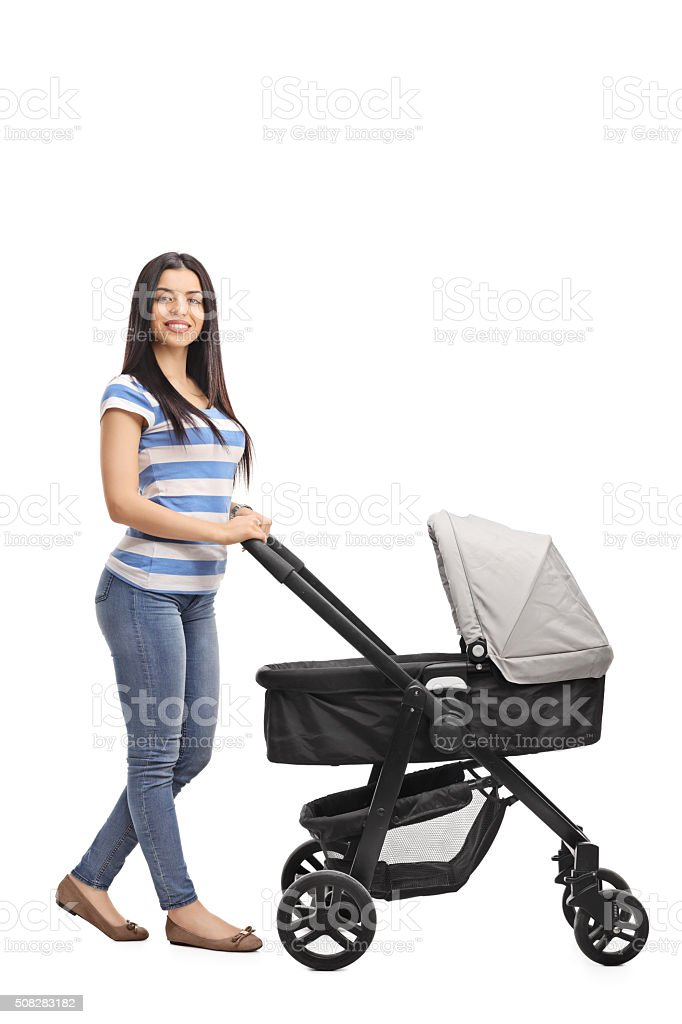 Cheerful mother pushing a baby stroller stock photo