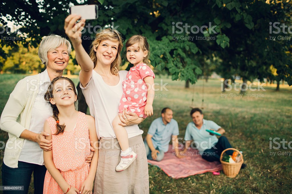 Cheerful Multi-Gebration Family Standing Outdoors And Making Selfie. stock photo
