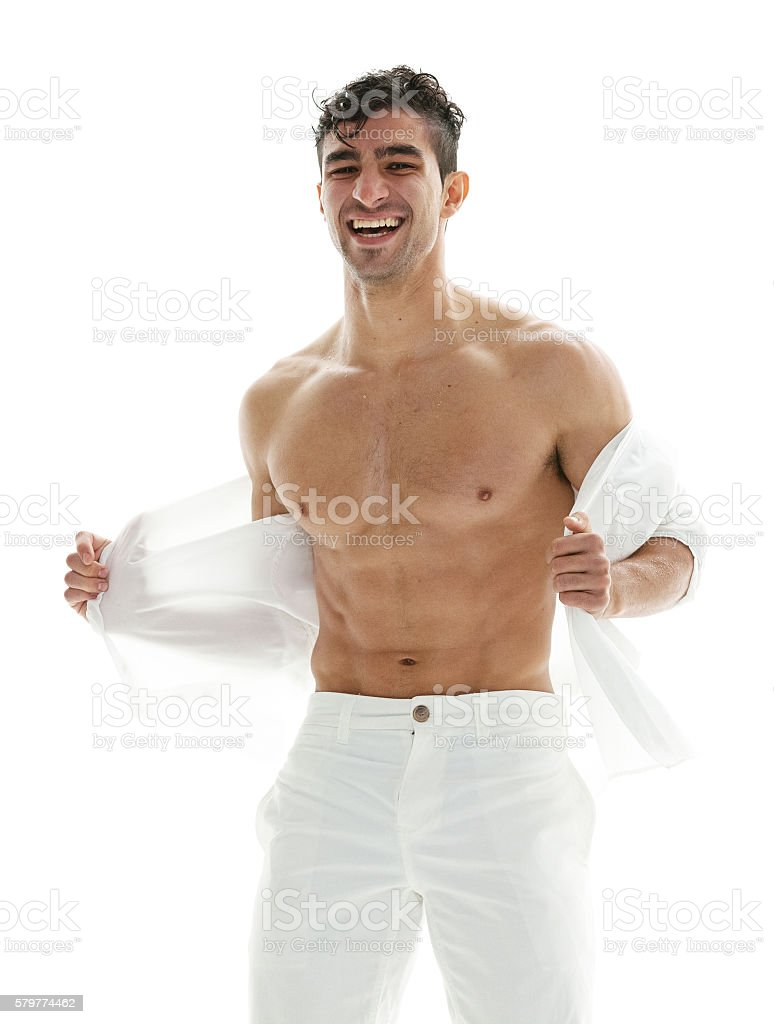 Cheerful muscular undressing stock photo