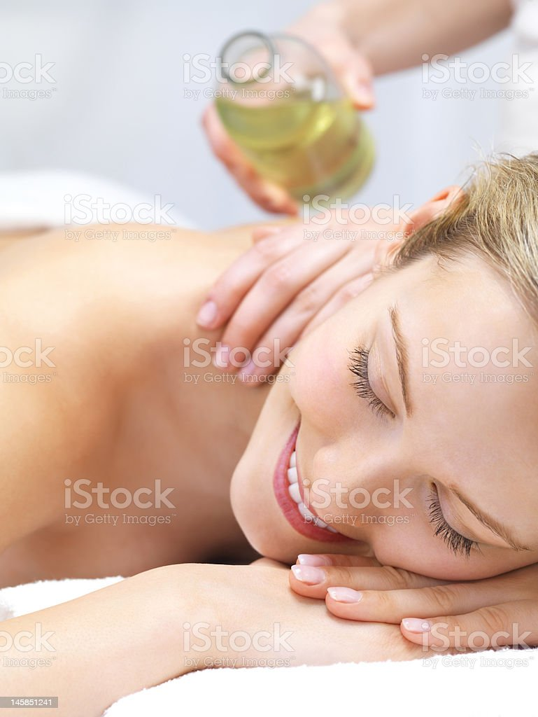 Cheerful naked young woman lying on front receiving message royalty-free stock photo