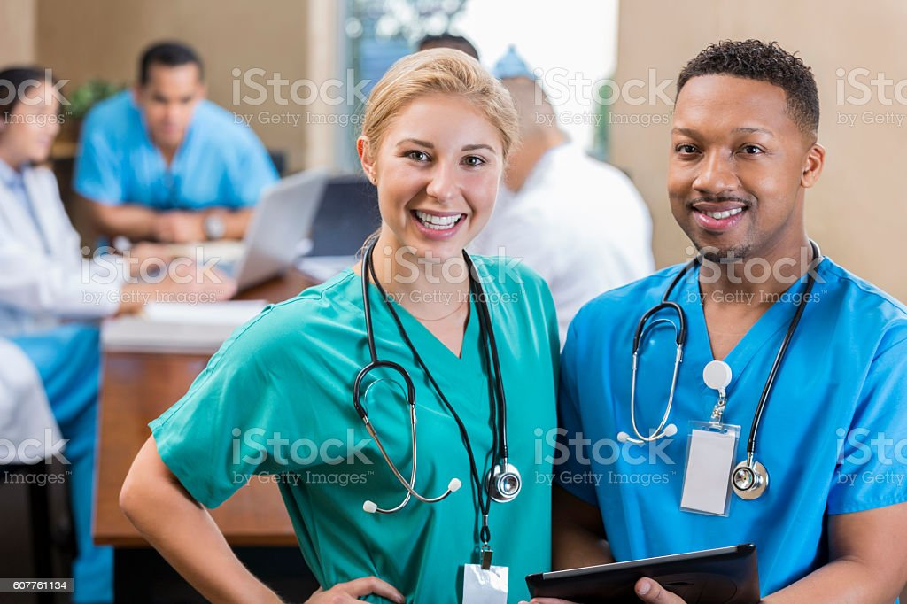 Cheerful nurse friends at hospital staff meeting stock photo