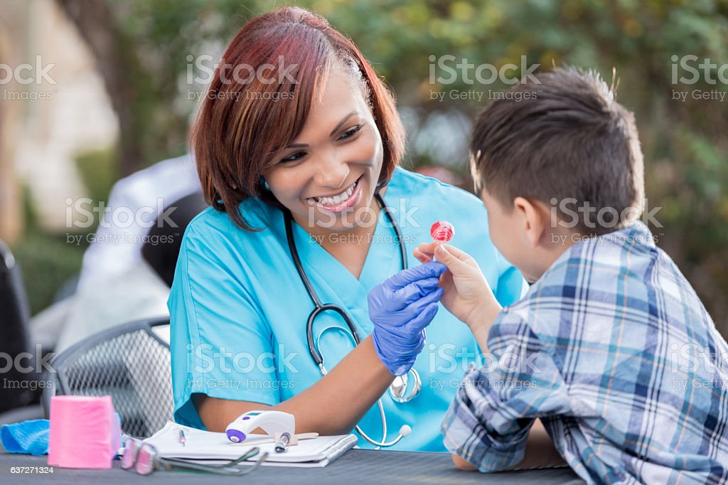 Mid adult African American nurse gives a young boy a lollipop after...