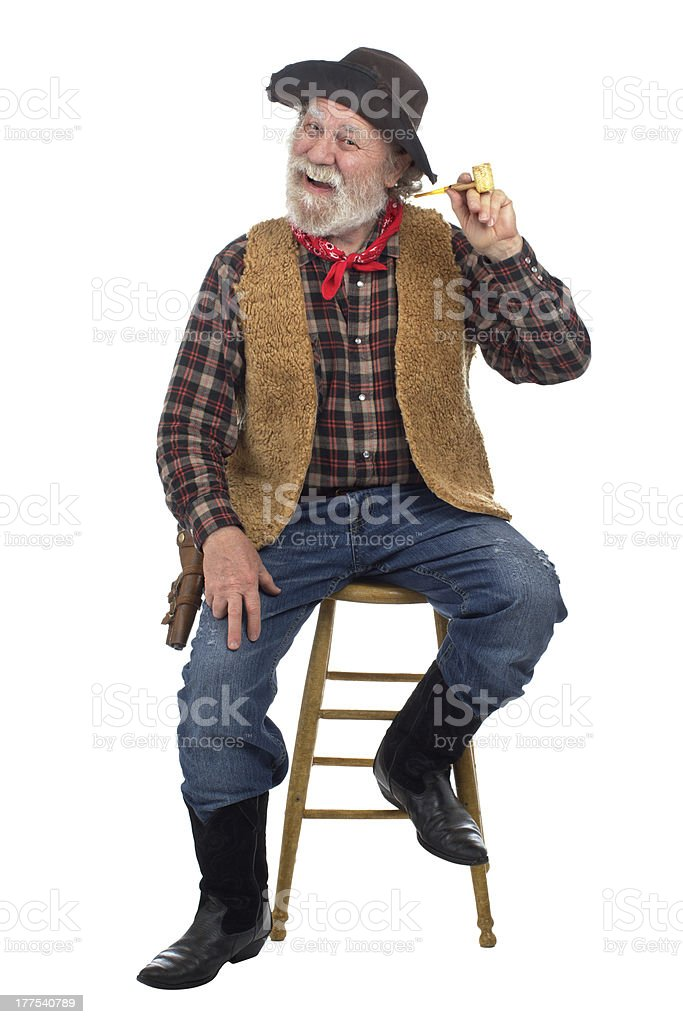 Cheerful old cowboy sits on stool with corn cob pipe stock photo